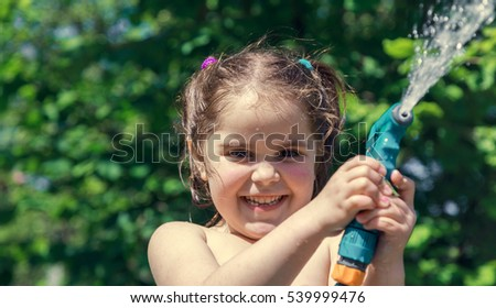 Little girl playing in the hot summer garden, spraying all around with water from a garden hose.