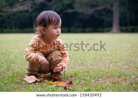 Little girl playing in the park crouched on her haunches.