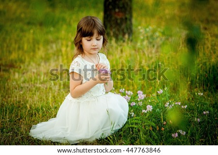 Little girl playing in the park with a toy