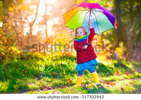 Little girl playing in the rain in autumn park. Child holding umbrella walking in the forest on a sunny fall day. Children playing outdoors with yellow maple leaf. Toddler girl picking golden leaves - stock photo