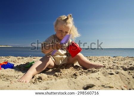 little girl playing in the sand on the beach by the sea. summer rest