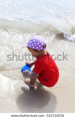 Little girl playing in water sea on the beach - stock photo
