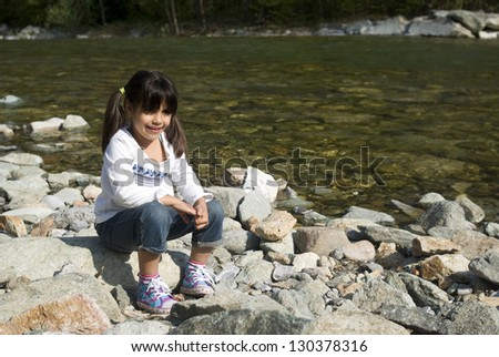 Little girl playing near the river