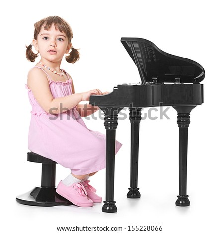 little girl playing on a miniature piano - stock photo