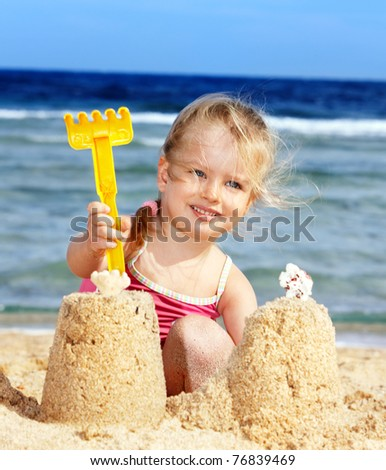 Little girl  playing on  beach. - stock photo