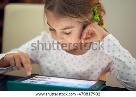 Little girl playing on her tablet at home