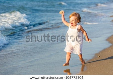 Little girl playing on the beach - stock photo