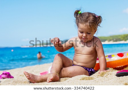 Little Girl Playing on the beach at the Aegean Sea.
