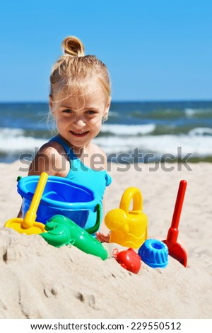 Little girl playing on the sand beach.