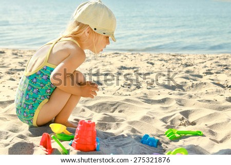 little girl playing on the sea shore - stock photo