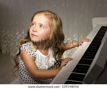 little girl playing piano in a white room - stock photo