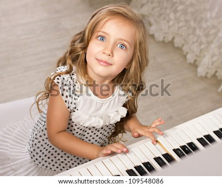 little girl playing piano looking at camera in light room - stock photo