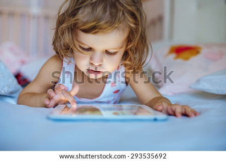 little girl playing tablet at home on a bed - stock photo