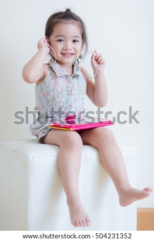Little Girl playing Tablet Computer at her house