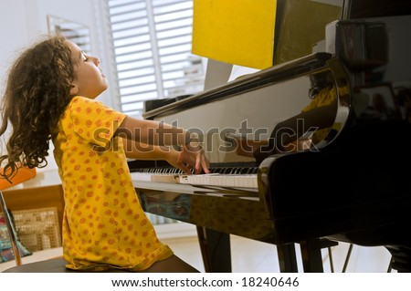 little girl playing the grand piano - stock photo