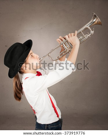 little girl playing trumpet on a gray background - stock photo