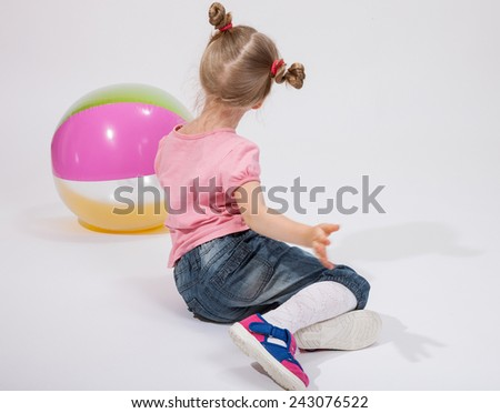 Little girl playing with a ball on the floor - stock photo