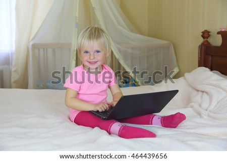 little girl playing with a laptop on the big bed