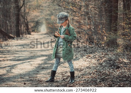 little girl playing with a slingshot in the woods, photo in vintage style - stock photo