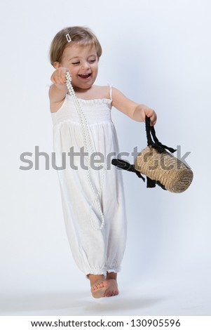 Little girl playing with bag and necklace. - stock photo