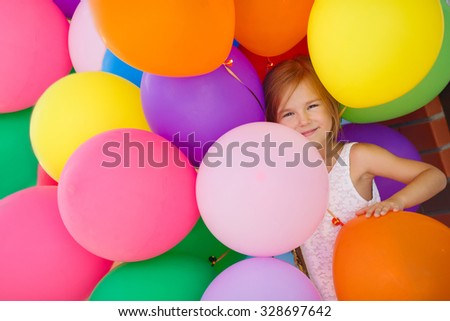 Little girl playing with balloons. Portrait of little girl playing with air balloons. Happy little girl holding colorful balloons.Smiling kid. happiness - stock photo