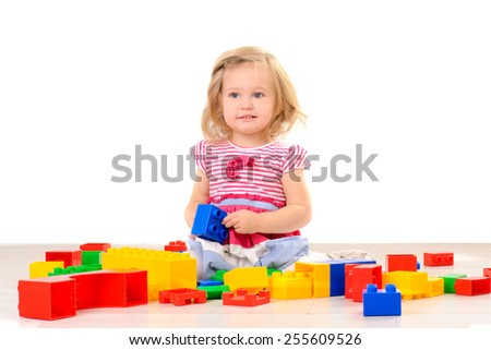 Little girl playing with colorful blocks on white background