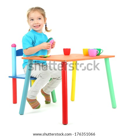 Little girl playing with colorful tableware isolated on white - stock photo