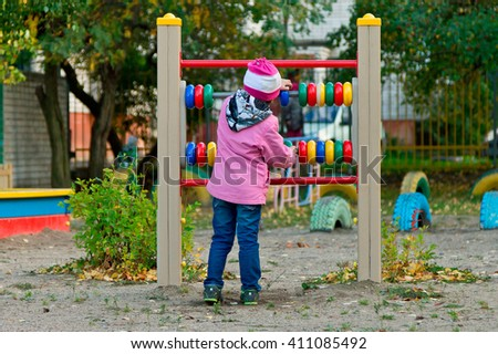 Little girl playing with colorful wooden abacus on playground