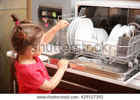 Little girl playing with dishwasher in kitchen