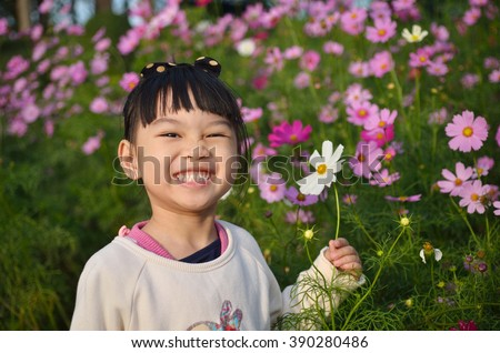 Little girl playing with flowers in the garden. Kids play outdoors in summer. Children gardening. Kid playing with plants. - stock photo
