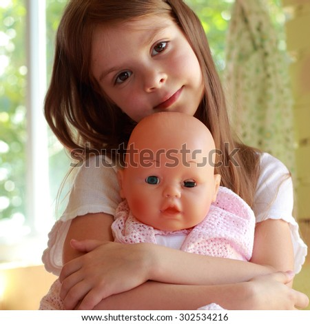 Little girl playing with her baby doll and pretending mom - stock photo