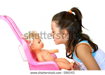Little girl playing with her doll - stock photo