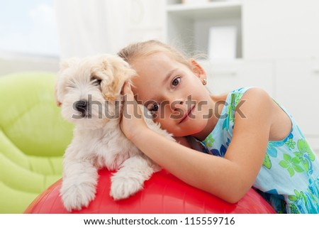 Little girl playing with her small fluffy dog at home - stock photo