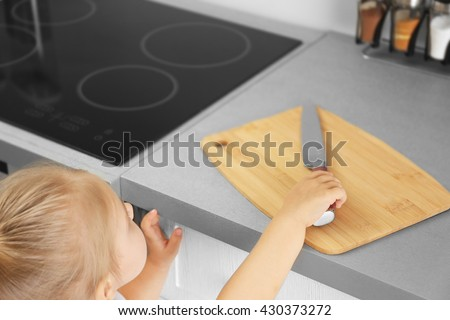 Little girl playing with knife in the kitchen - stock photo