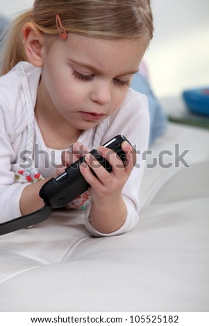 Little girl playing with mobile telephone - stock photo