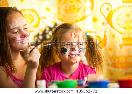 Little girl playing with painting with sister. - stock photo