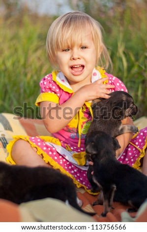 Little girl playing with puppies - stock photo