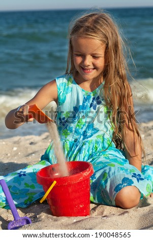 Little girl playing with sand on the sunny beach sitting