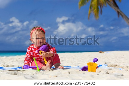 little girl playing with sand on tropical beach