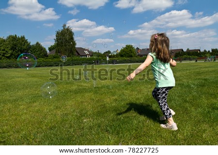 Little girl playing with soap bubbles - stock photo