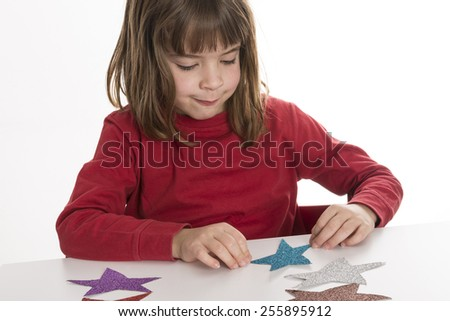 Little girl playing with stars made of paper with glitter colors - stock photo