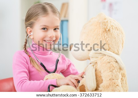 Little girl playing with stethoscope - stock photo