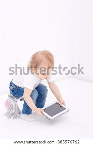 Little girl playing with tablet computer. Mobile technology. Happy childhood. - stock photo