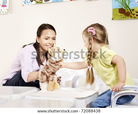 Little girl playing with teacher in preschool. - stock photo