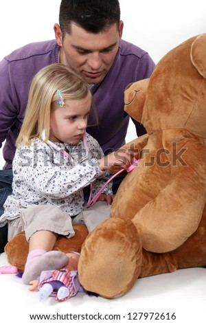 Little girl playing with teddy bear - stock photo