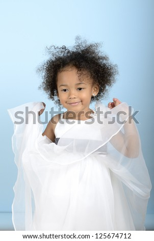little girl playing with the layers of her dress - stock photo