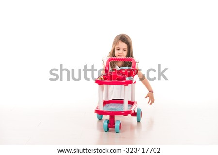 Little girl playing with toy pram with cups home - stock photo