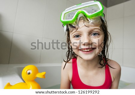little girl playing with toys in a bath - stock photo
