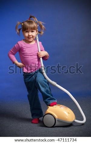 little girl playing with vacuum cleaner toy - stock photo