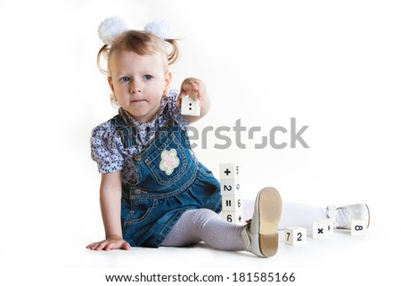 little girl plays cubes isolated in white background